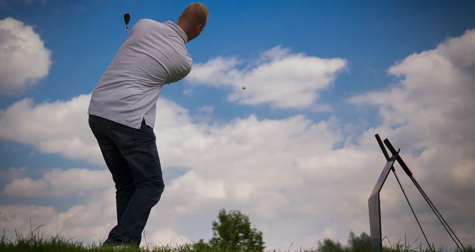 Image showing a low angle snap of a player playing his shot  where the ball is shown flying in the air representing the popular golf point game, Trouble